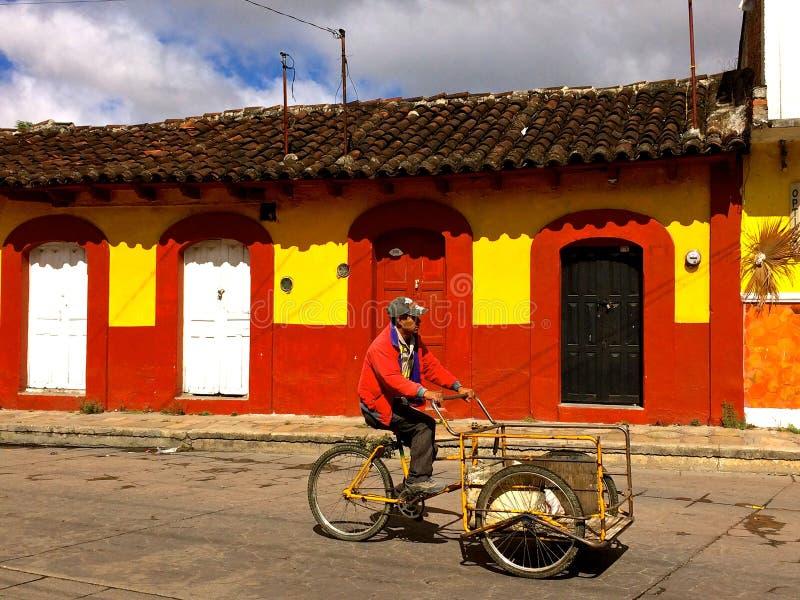 Homme avec la bicyclette de la livraison devant les maisons coloniales colorées dans San Cristobal de Las Casas images stock