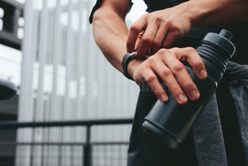 Homme avec la bouteille d'eau utilisant un smartwatch pour surveiller son progrès image libre de droits