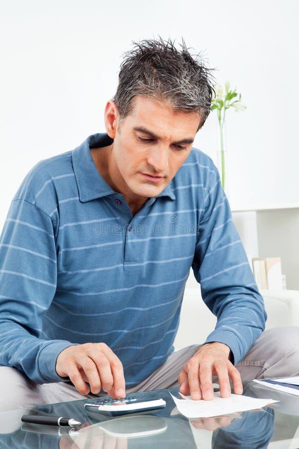 Homme avec la calculatrice et les factures image stock