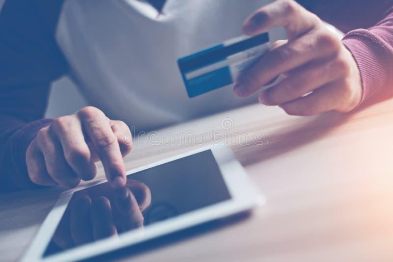 Homme avec la carte de crédit faisant des achats d'Internet utilisant la tablette photographie stock libre de droits