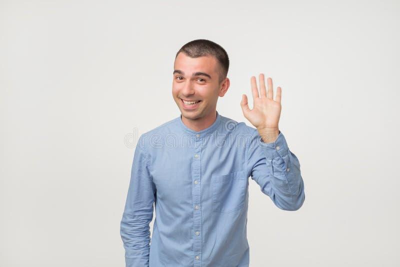 Homme avec la chemise bleue disant le bonjour, ondulant une main images libres de droits