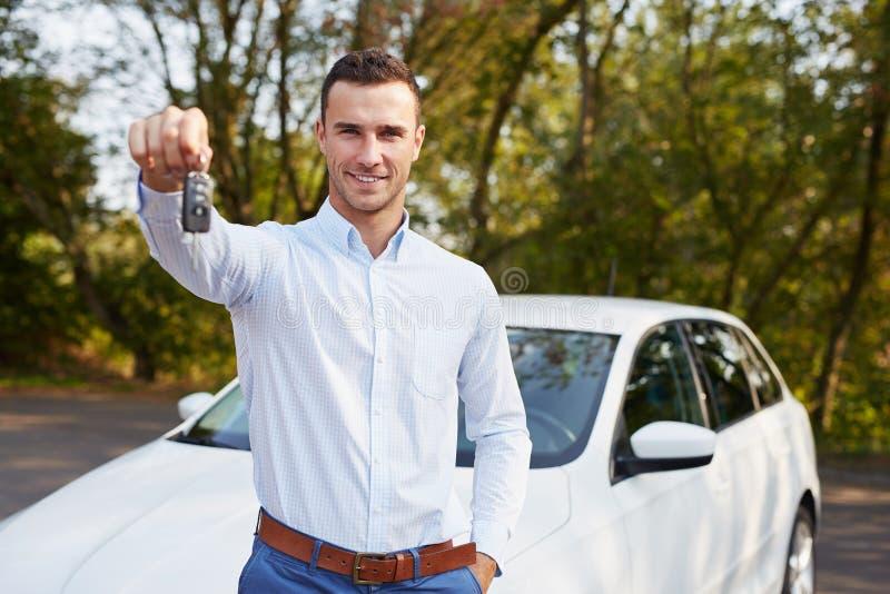 Homme avec la clé se tenant devant la voiture photographie stock