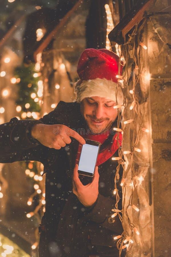 Homme avec la décoration futée de téléphone d'écran vide et de lumières de Noël Concept de technologie et de vacances image libre de droits