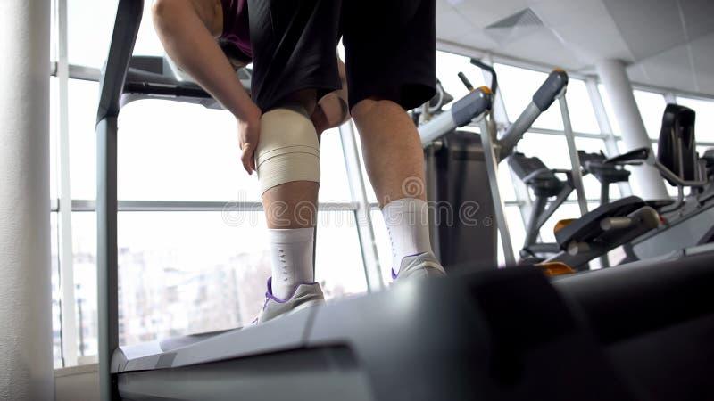 Homme avec la douleur de bandage de genou de la douleur, se tenant sur le tapis roulant, réadaptation photos stock