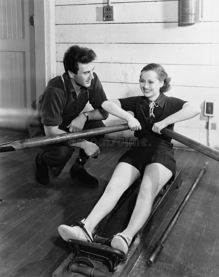 Homme avec la femme à l'aide de la machine à ramer (toutes les personnes représentées ne sont pas plus long vivantes et aucun dom image libre de droits