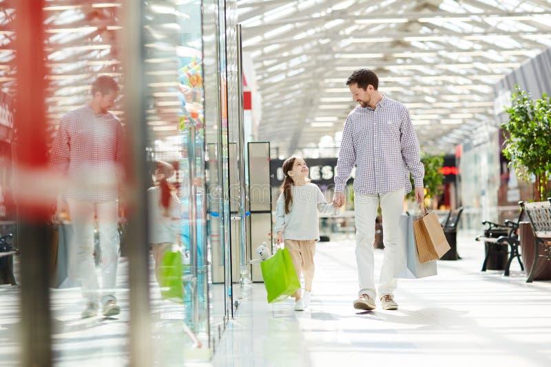 Homme avec la fille marchant dans le centre commercial images libres de droits
