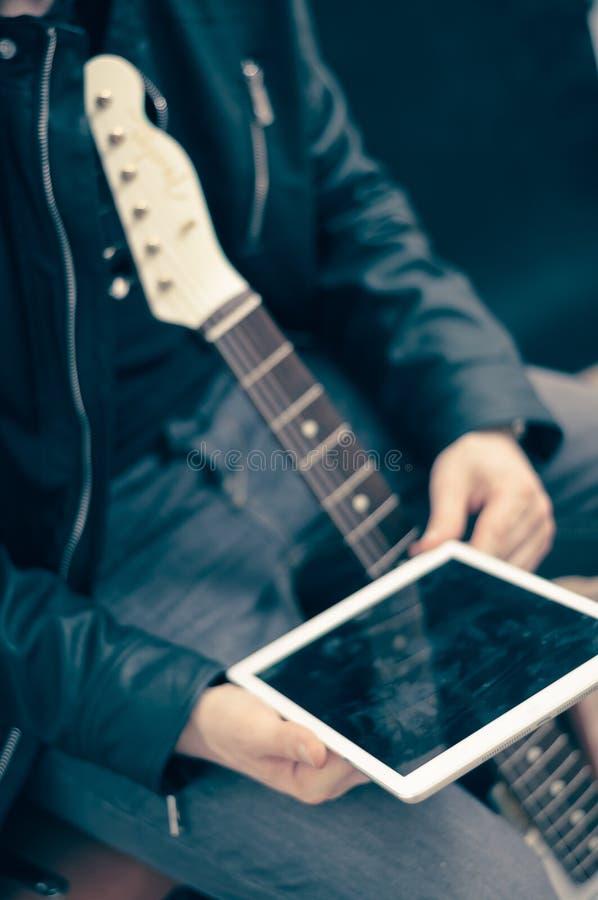 Homme avec la guitare électrique et l'ipad photos stock