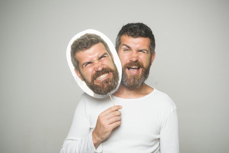 Homme avec la longue barbe sur cligner de l'oeil et la plaque signalétique fâchée de visage photo stock
