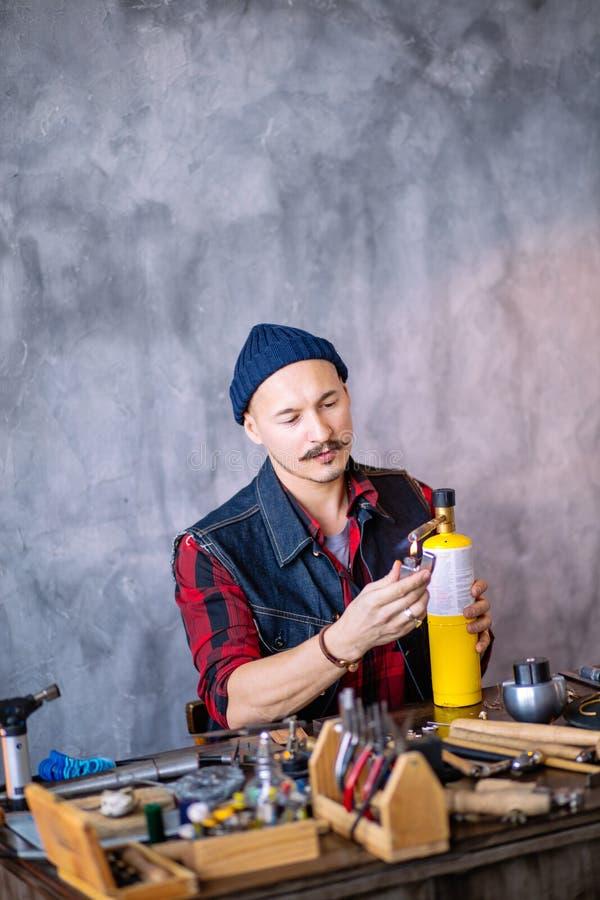 Homme avec la moustache, le chapeau, le gilet et la chemise préparant des outils pour fondre les articles d'or photo libre de droits