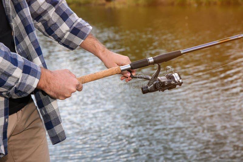 Homme avec la pêche de tige à la rive, foyer sur des mains image libre de droits