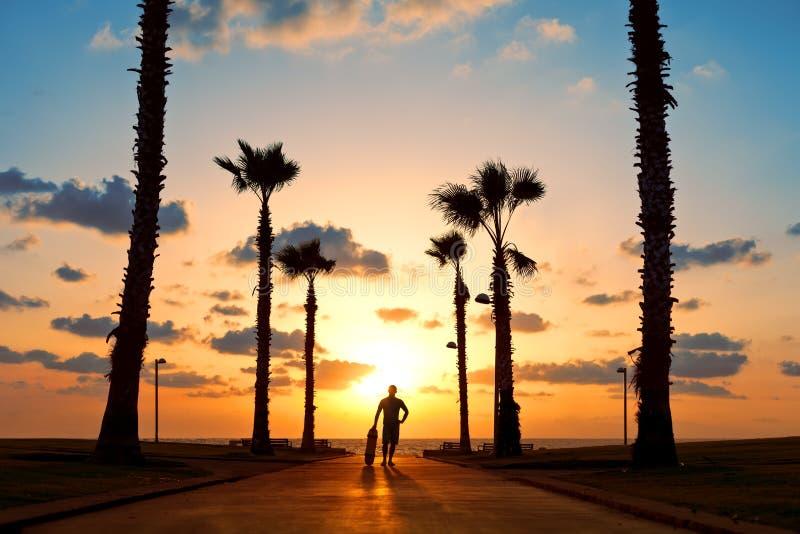 Homme avec la planche à roulettes dans le coucher du soleil image stock
