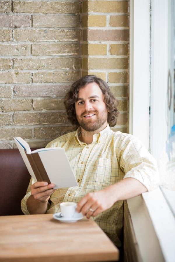 Homme avec la tasse de livre et de café se reposant dans le cafétéria images libres de droits