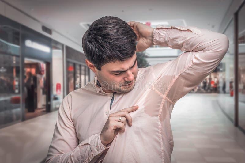 Homme avec la transpiration sous l'aisselle au centre commercial images stock