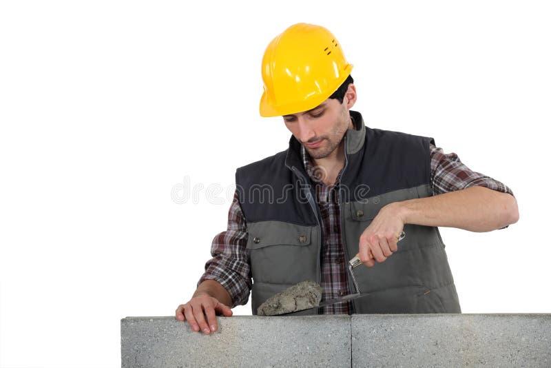 Homme avec la truelle et le ciment image libre de droits