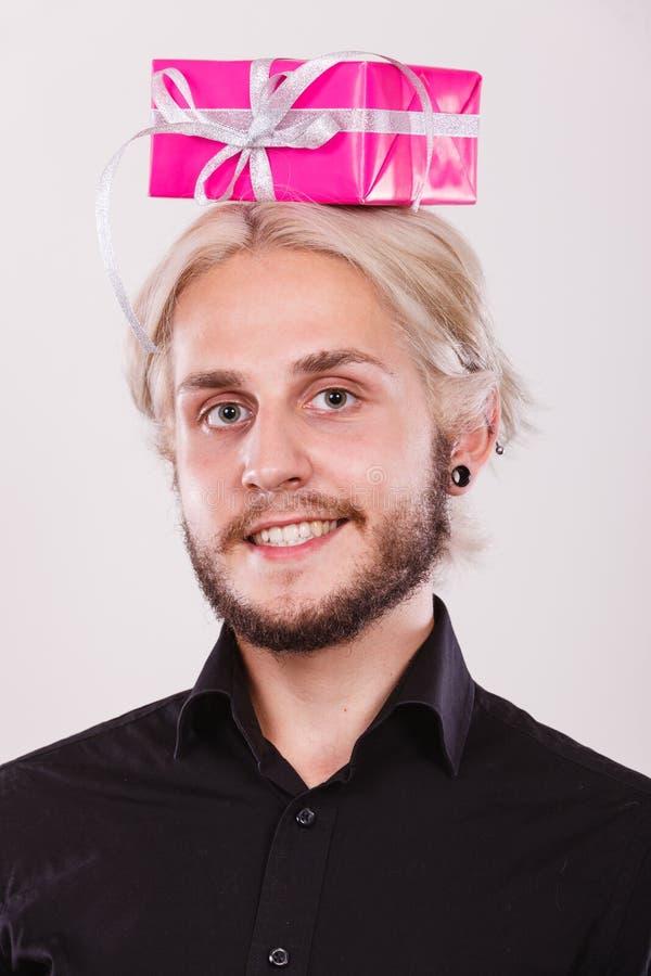 Homme avec le boîte-cadeau rose sur sa tête image libre de droits