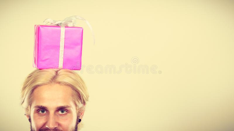 Homme avec le boîte-cadeau rose sur sa tête photos libres de droits
