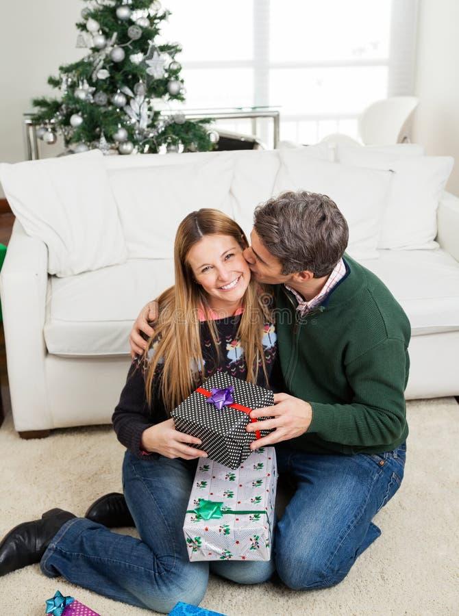 Homme avec le cadeau de Noël embrassant la femme sur la joue images stock