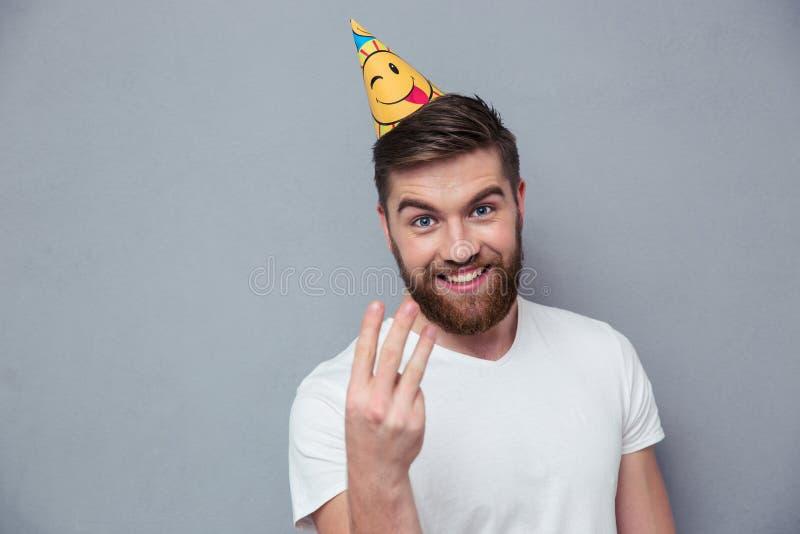 Homme avec le chapeau d'anniversaire montrant trois doigts image stock