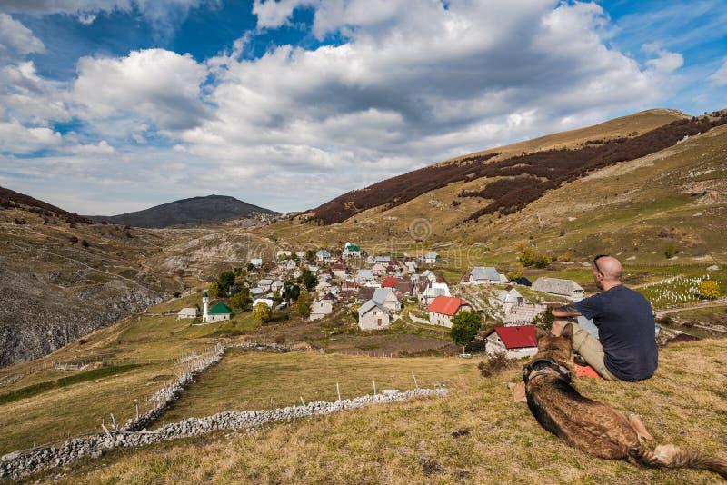 Homme avec le chien regardant le panorama de village de Lukomir, Bosnie photo libre de droits