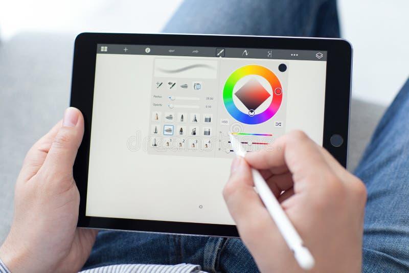 Homme avec le crayon d'Apple jugeant dans l'iPad de main pro photographie stock