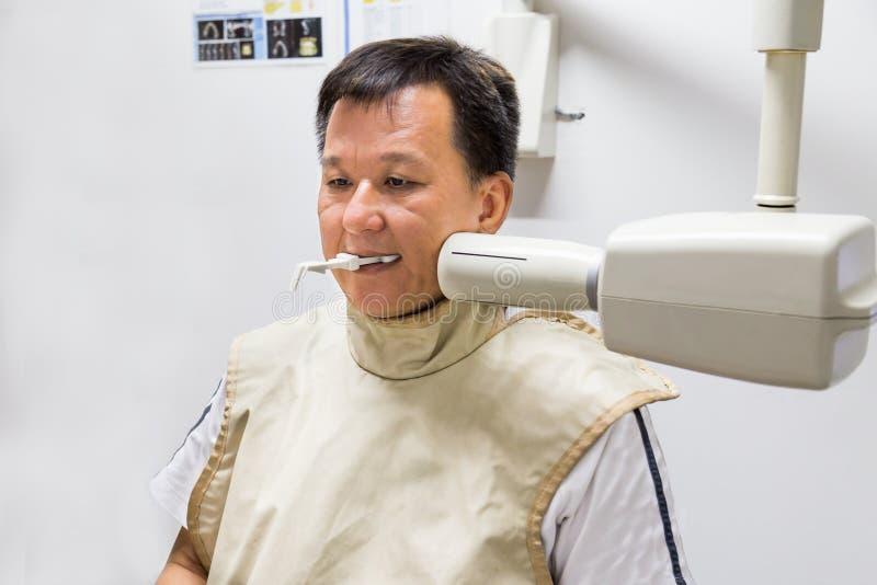 Homme avec le gilet de radioprotection recevant le rayon X dentaire à un dentiste photos libres de droits