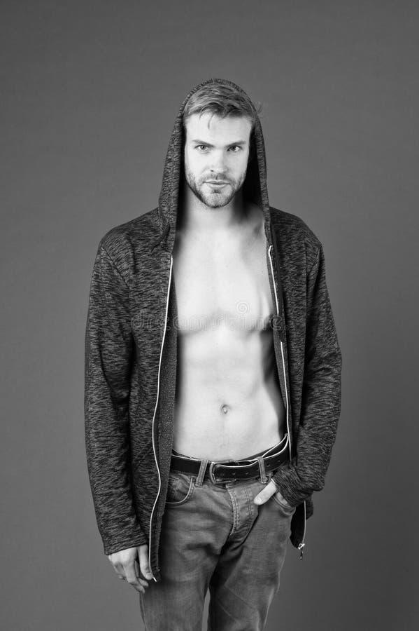 Homme avec le hoodie de port de torse nu Hippie avec la barbe élégante équilibrée dans des jeans gris Type avec le corps musculai photo libre de droits
