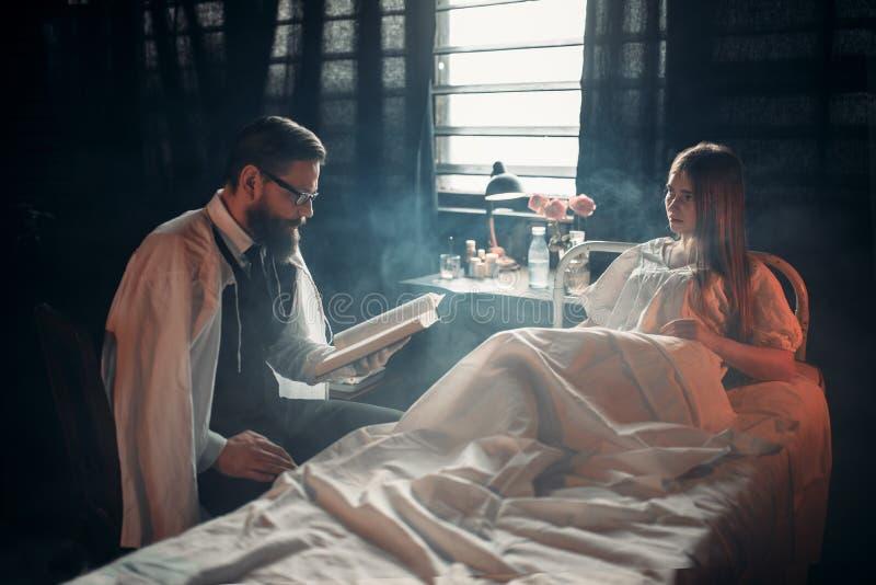 Homme avec le livre contre la femme malade dans le lit d'hôpital image stock