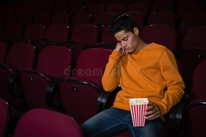 Homme avec le maïs éclaté dormant dans le théâtre photo stock