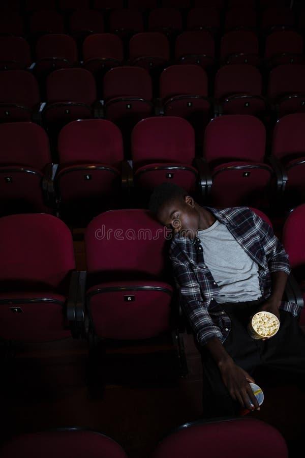 Homme avec le maïs éclaté dormant dans le théâtre photographie stock libre de droits