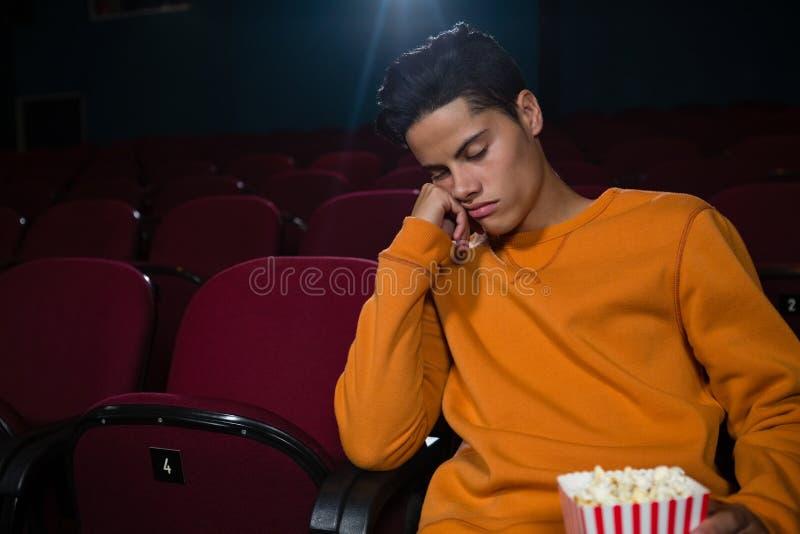 Homme avec le maïs éclaté dormant dans le théâtre photos stock