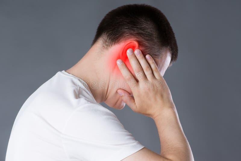 Homme avec le mal d'oreille, douleur aux oreilles sur le fond gris image libre de droits