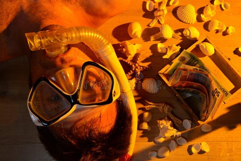 Homme avec le masque de scaphandre et l'argent de vacances photo stock