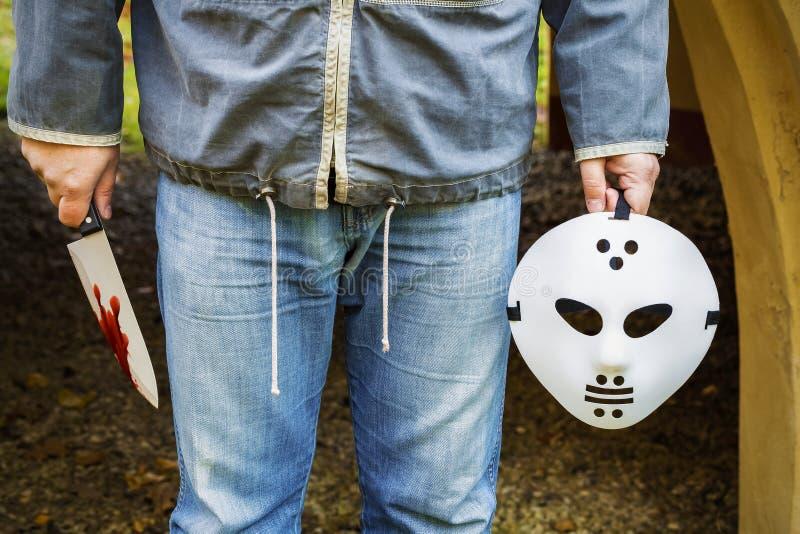 Homme avec le masque effrayant de Halloween et couteau dans le sang photographie stock libre de droits
