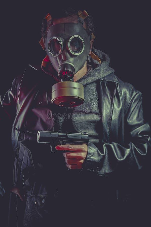Homme avec le masque et l'arme à feu de gaz, habillés dans la veste en cuir noire photo libre de droits