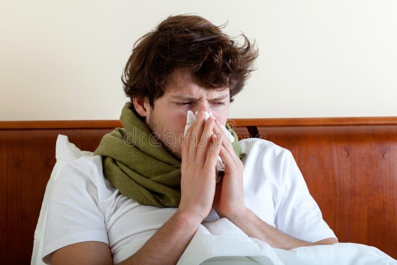 Homme avec le nez courant dans le lit photographie stock libre de droits