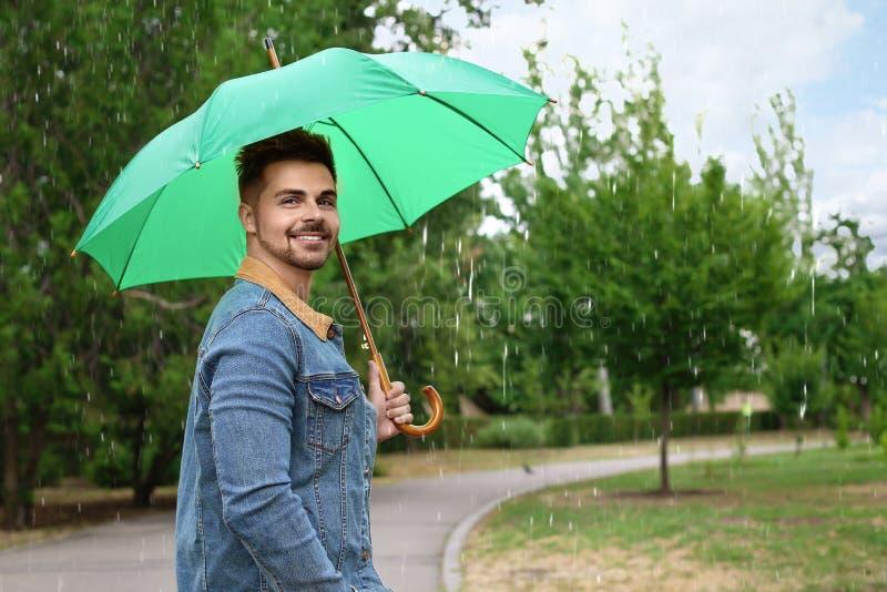 Homme avec le parapluie dehors sur pluvieux image stock