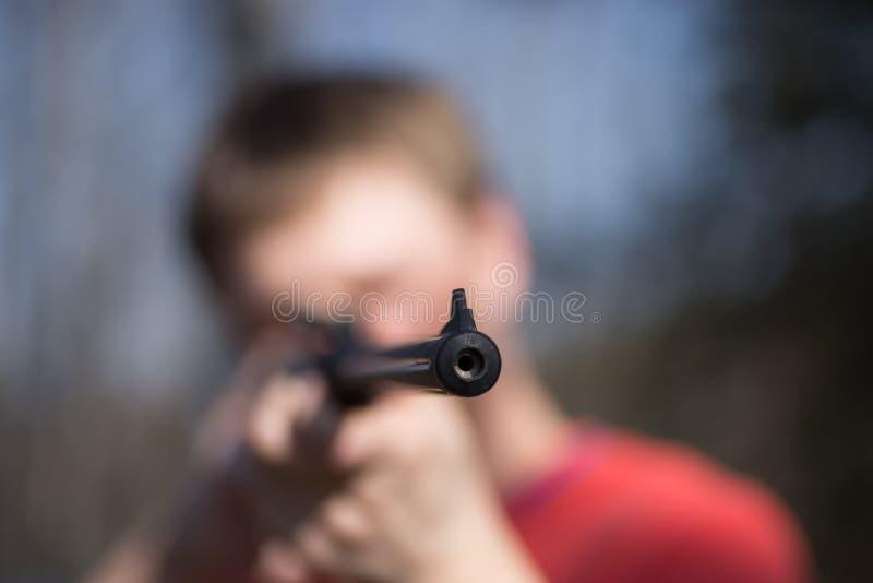 Homme avec le pistolet pneumatique dans la forêt photographie stock