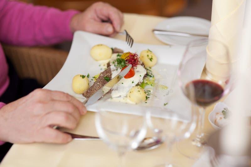 Homme avec le plat tenant la fourchette et le couteau au Tableau de restaurant images stock