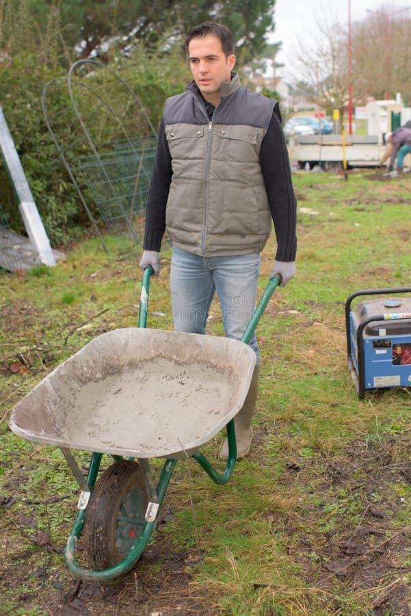 Homme avec le plein travail de ciment de brouette dans le jardin image stock