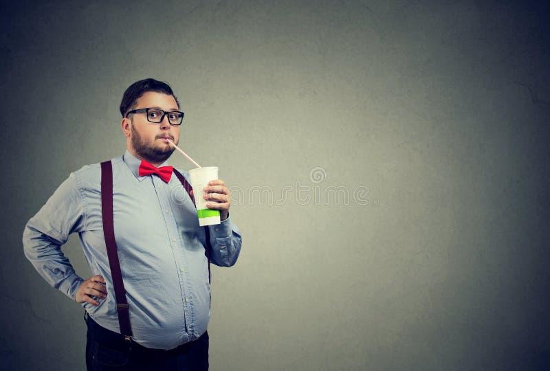 Homme avec le poids excessif buvant la soude douce photos stock