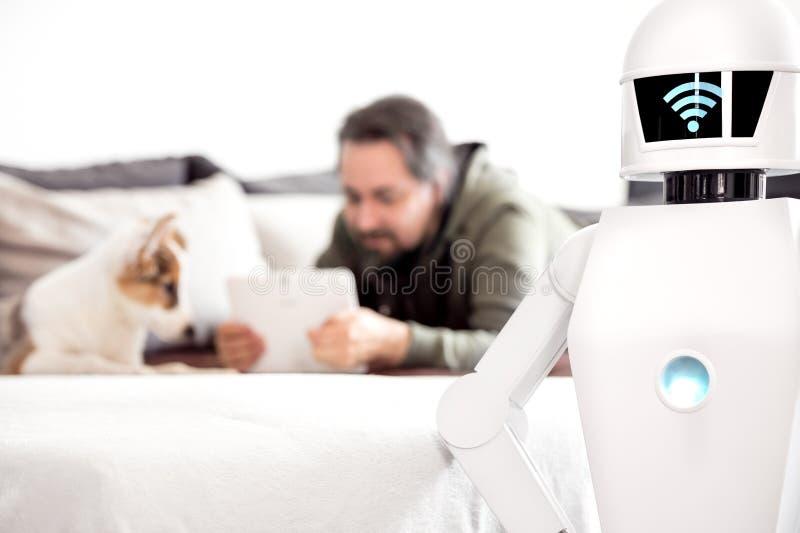 Homme avec le robot de service dans le salon images stock