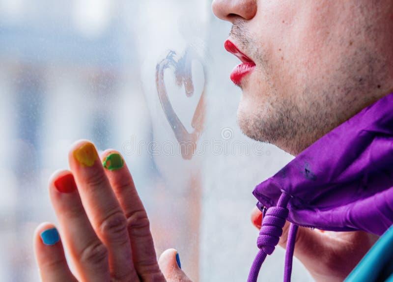 Homme avec le séjour d'ongle de rouge à lèvres et de poli près de la fenêtre misted avec le coeur de dessin photographie stock
