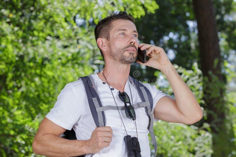 Homme avec le sac à dos et les jumelles utilisant le smartphone dans la campagne photographie stock libre de droits
