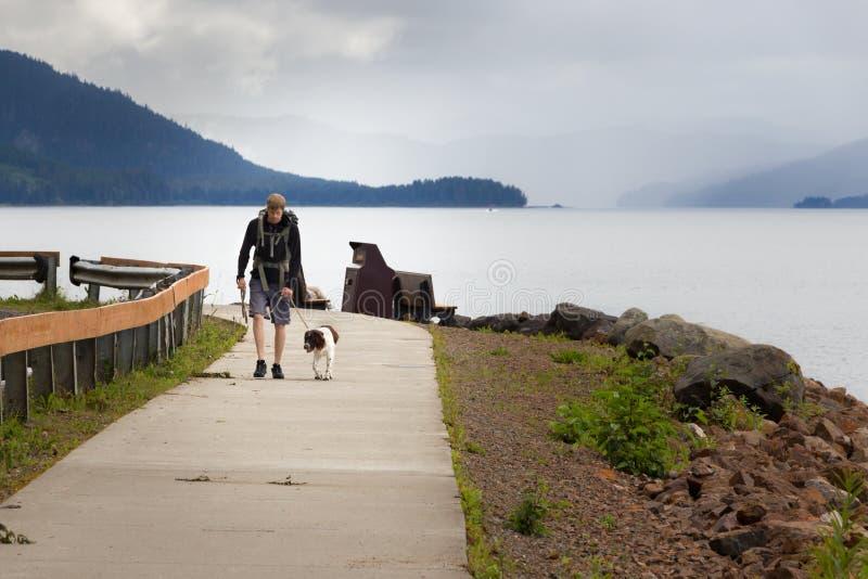 Homme avec le sac à dos marchant avec son chien dans la route glaciale de point de détroit, photographie stock libre de droits