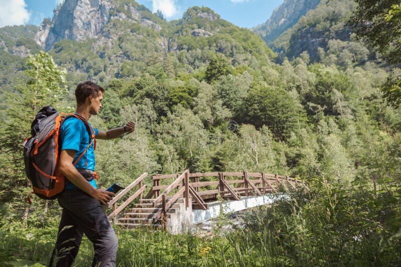 Homme avec le sac à dos observant sa montre entourée par la nature étonnante photo libre de droits