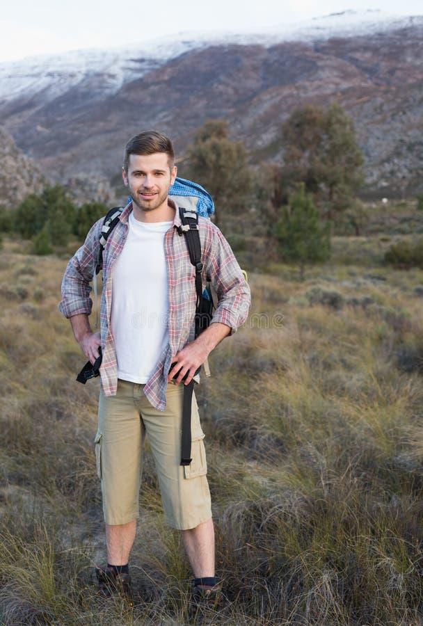 Homme avec le sac à dos se tenant sur le paysage de forêt photos stock
