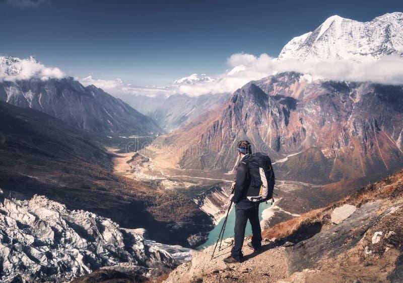 Homme avec le sac à dos sur la crête de montagne au coucher du soleil photographie stock libre de droits