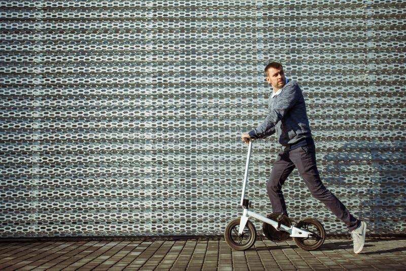 Homme avec le scooter devant le bâtiment photos libres de droits