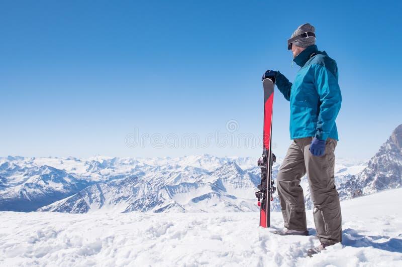 Homme avec le ski sur le dessus de montagne photographie stock