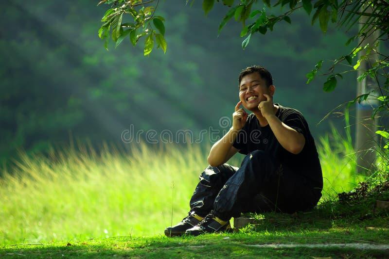 Homme avec le sourire sous l'arbre images libres de droits